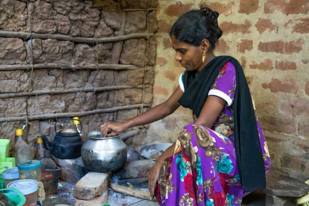 Fausiya is wearing a purple dress with a floral print and a black scarf. She is kneeling down and is cooking in her kitchen.