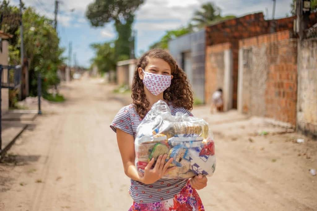 Germina is wearing a gray and black striped shirt with a red floral print skirt and a face mask. She is holding a basket of food that was given to her family by the Compassion center. She is standing on a dirt road in her neighborhood.