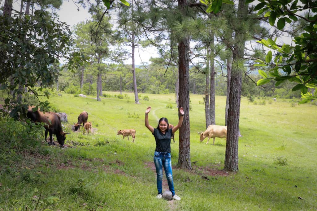 Girl wearing a black blouse with little blue flowers on it. She's also wearing jeans and white tennis shoes. She is standing in a field with cows and she is holding her hands in the air.