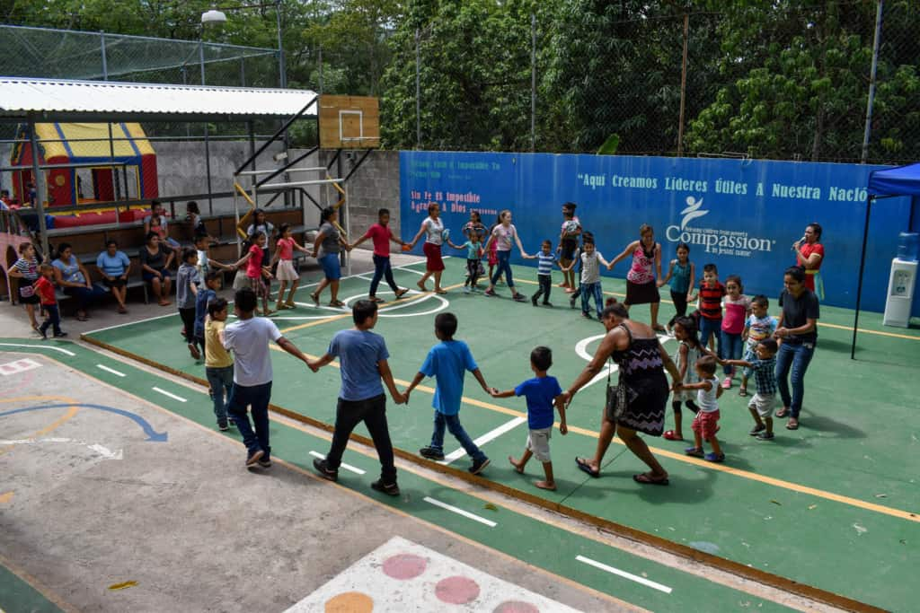 Children hold hands and walk in a circle as part of an activity.