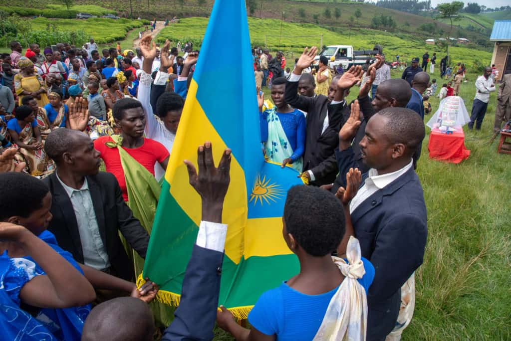 A group of men and women are holding the Rwandan flag on one hand and raising the other while making their vows during the marriage ceremony.