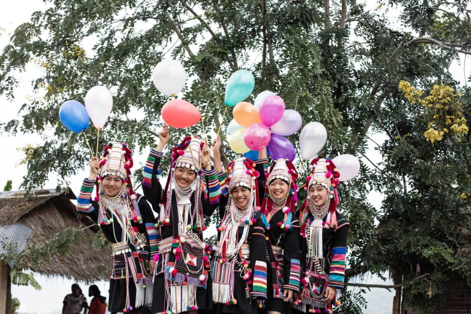 A group of women standing on the back of a truck, wearing their Akha traditional custom dress and hats, holding colorful balloons and smiling.