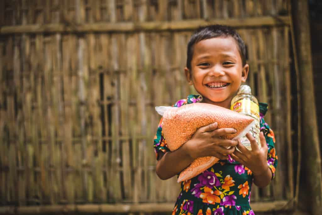 Girl wearing a green dress with a floral print. She is standing in front of a bamboo wall and is holding food she received from the Compassion center.