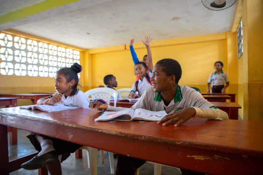 Steven (front right) and other children wearing white, green and black uniforms are sitting at long red desks, tables in a classroom with yellow walls. There are books on the tables in front of them. Steven is smiling and looking to the side. Two children in the background are raising their hands.