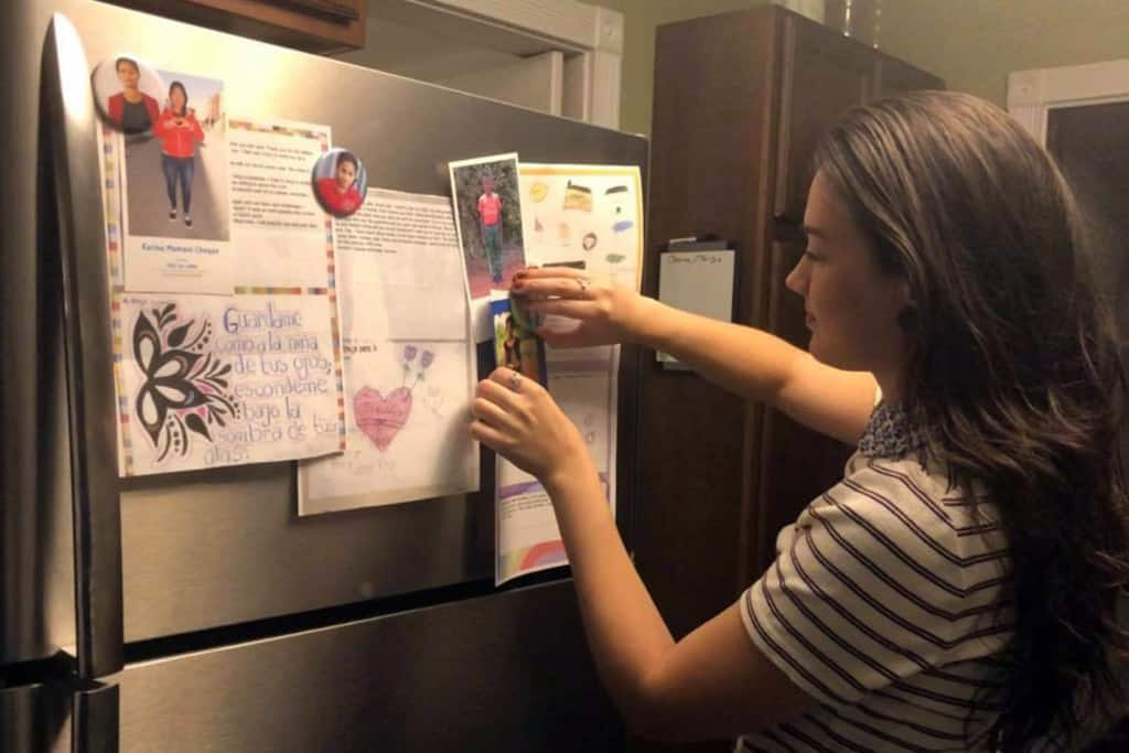 Katie hangs a photo of her sponsored child on her refrigerator.