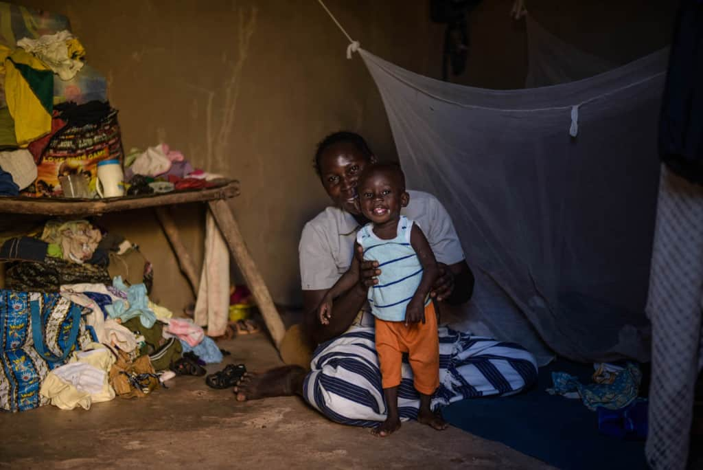 A mother and her toddler are siiting inside their home. On the left is a wooden table with clothes and other household belongings. Behind them is a mosquito net hanging from the wall.