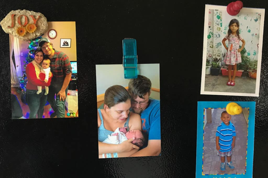 Sarah's black refrigerator door shows four family photos, including photos of the children the sponsors.
