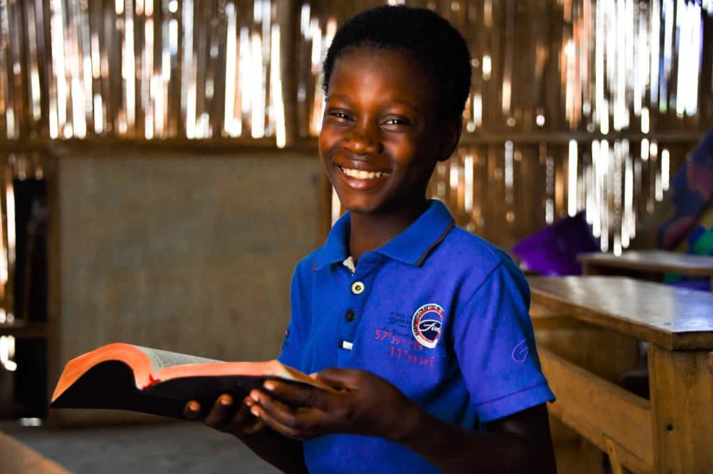 Deborah is wearing a blue shirt. She is sitting inside the Compassion center and is holding a Bible. She is sitting at a wooden table.