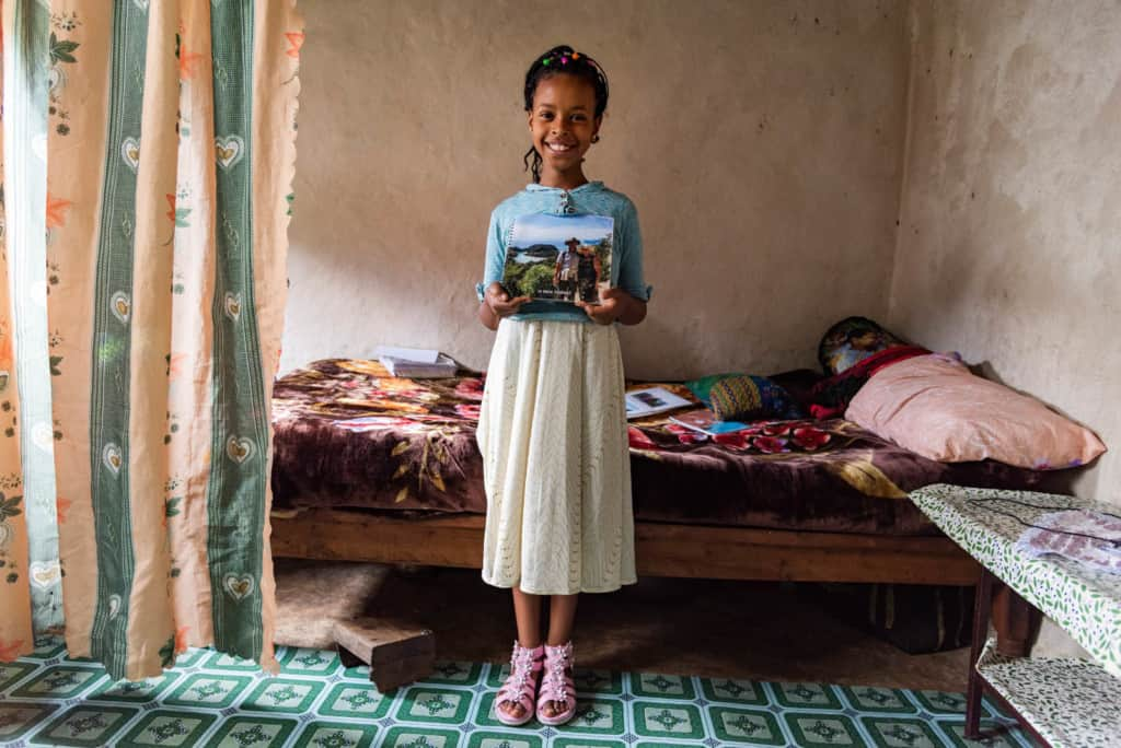 Girl wearing a blue shirt and white skirt. She is standing in her home in front of her bed, holding pictures of her sponsors.