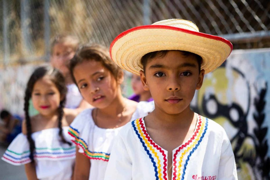 A boy in a white shirt and a straw hat with red trim is standing in front of two girls next to a chain link fence.