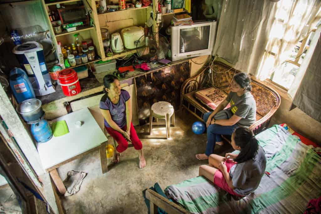 A mother and daughter are visited by a Compassion project director. They are sitting together in their small house.