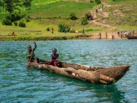 Two children are in a wood canoe on a lake. There are more people unloading items from another boat in the background.