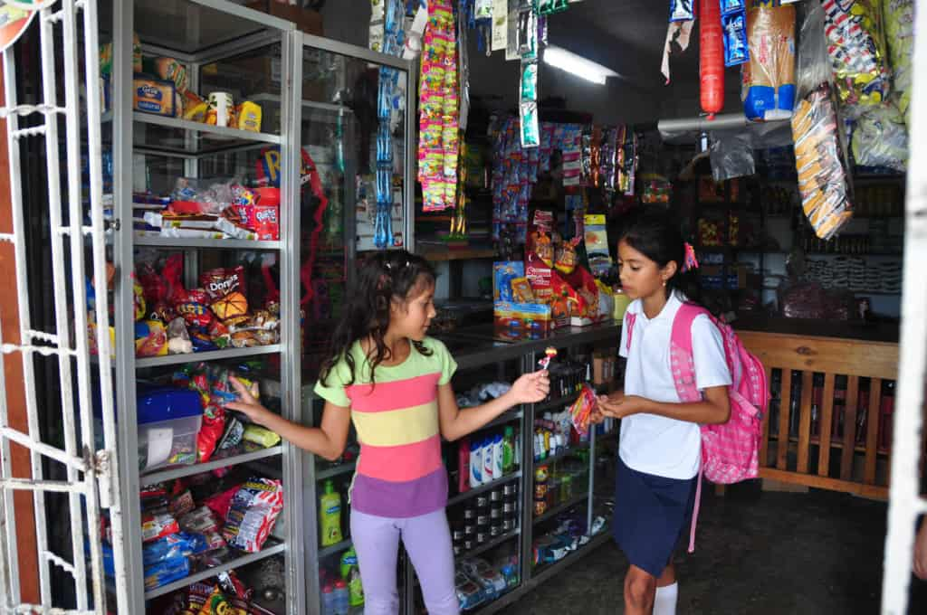 A 9 year old girl wearing a colorful striped shirt, stands beside a counter market store shelf shopping for candy as she shows her friend standing beside her who is wearing a white shirt and pink backpack a lollipop in her hand. Candy and other food supplies on shelves and hang around the store all around them.
