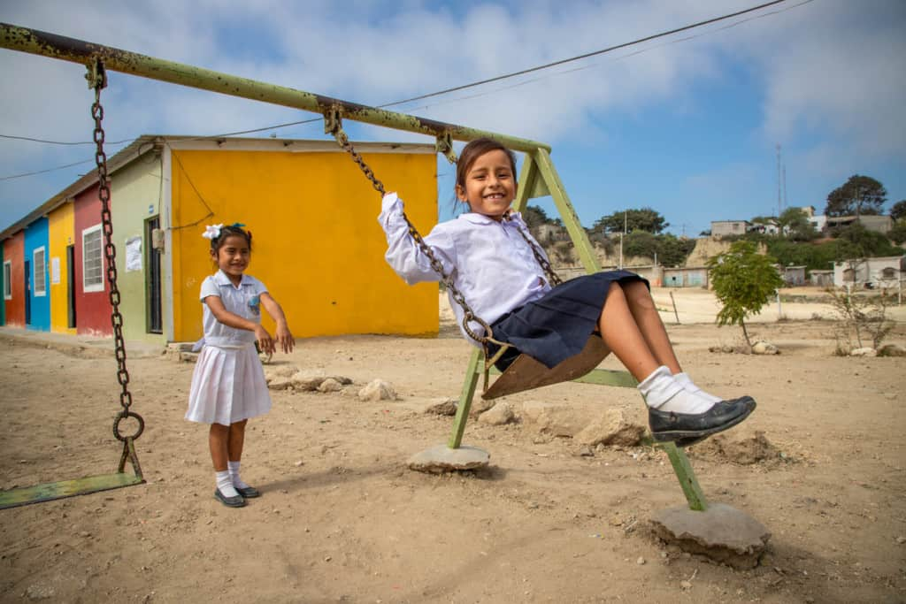 Girl wearing a white shirt and black skirt. She is sitting on a swing while her friend pushes her. The school building is behind them.