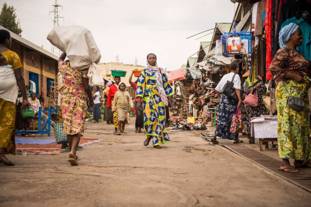 A woman walks through the marketplace in her local neighborhood. She is wearing colorful clothing. Many people are shopping and walking around her.