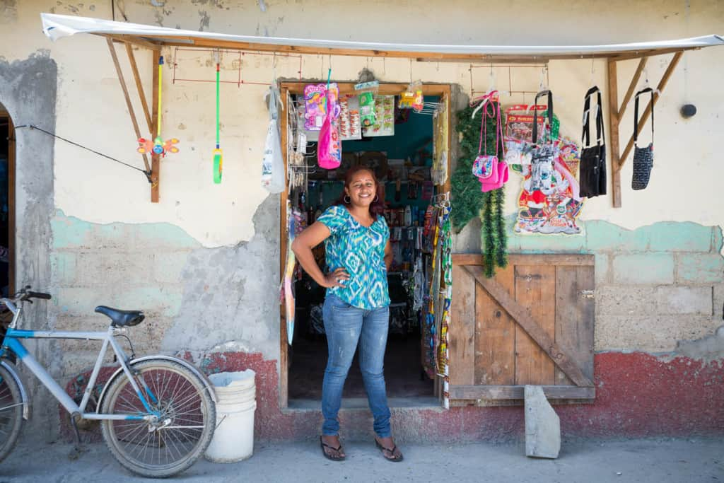 Woman wearing a blue shirt and jeans stands smiling looking out from the back of her market shop selling goods merchandise food snacks in a small building.