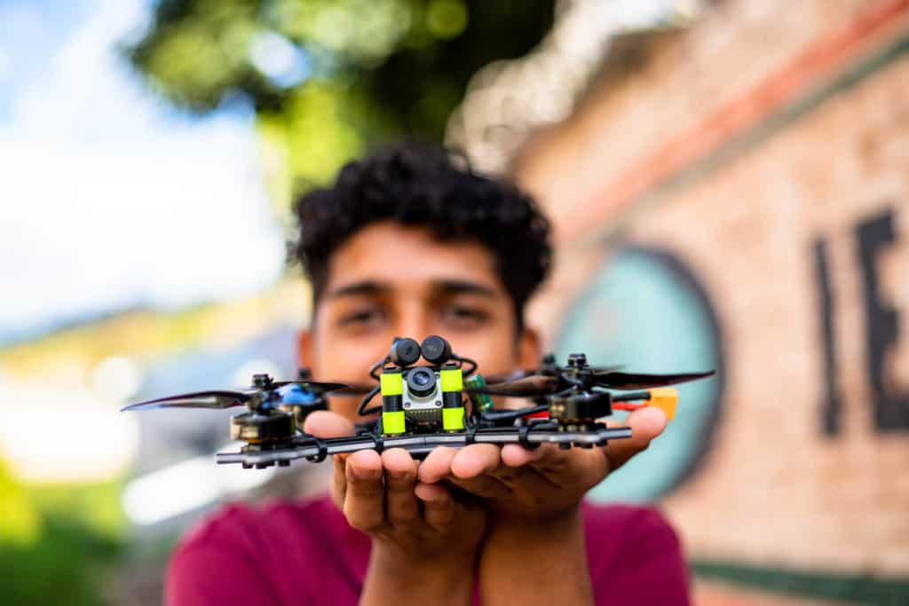 Miguel, in a red shirt, is outside the Compassion center holding the drone he learned to assemble through the center's training. Miguel's face is out of focus.