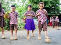 Four children in matching button-up shirts with brightly colored geoemetric patterns are playing a game where they walk on halved coconut shells, which are attached to ropes that they are holding with their hands.