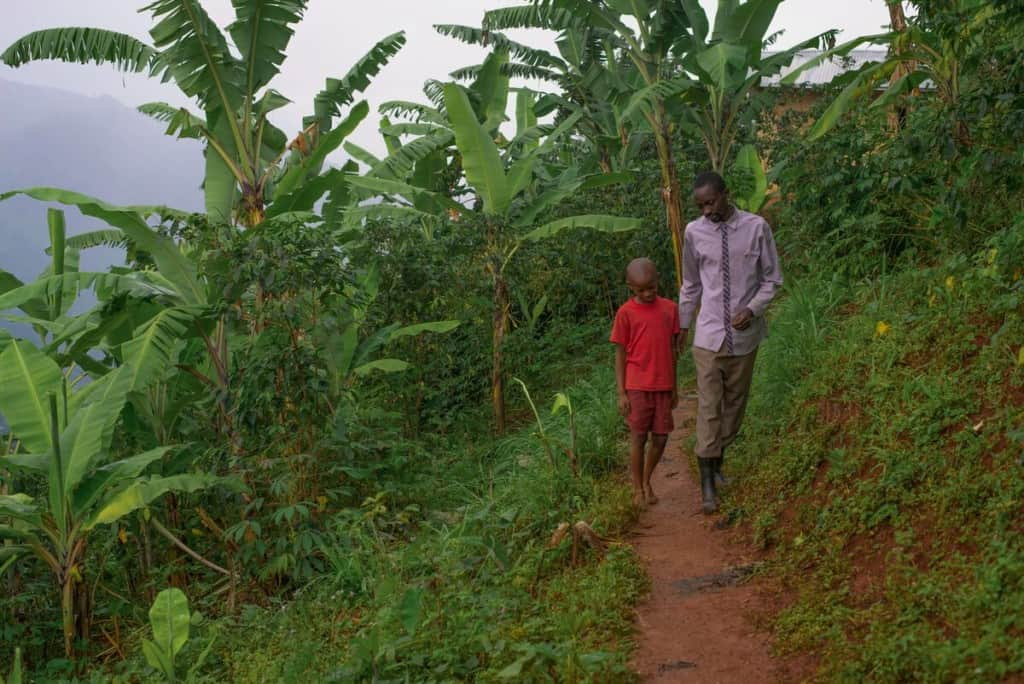 A father and son in Uganda walk down a narrow, red dirt trail leading through thick green foliage. The boy is wearing a red shirt and red shorts. The father is wearing a purple shirt and rainboots.