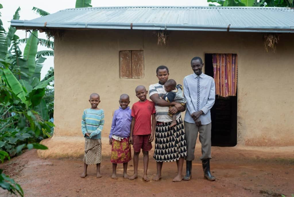 A family of six people stands outside their home in Uganda. The mother is holding a baby. The father is wearing rain boots. The mother and children are wearing colorful clothing and are barefoot.