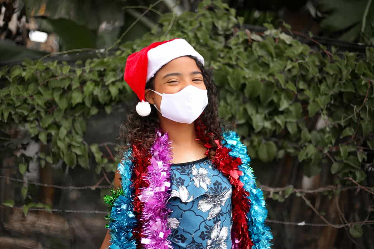 A girl in Brazil wears a white face mask, Santa hat and sparkly garlands around her shoulders.