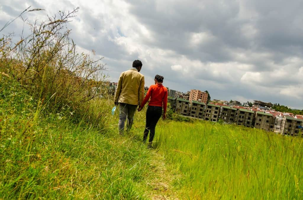 A man and a girl walk through a grassy field holding hands. There are rows of buildings in the background.