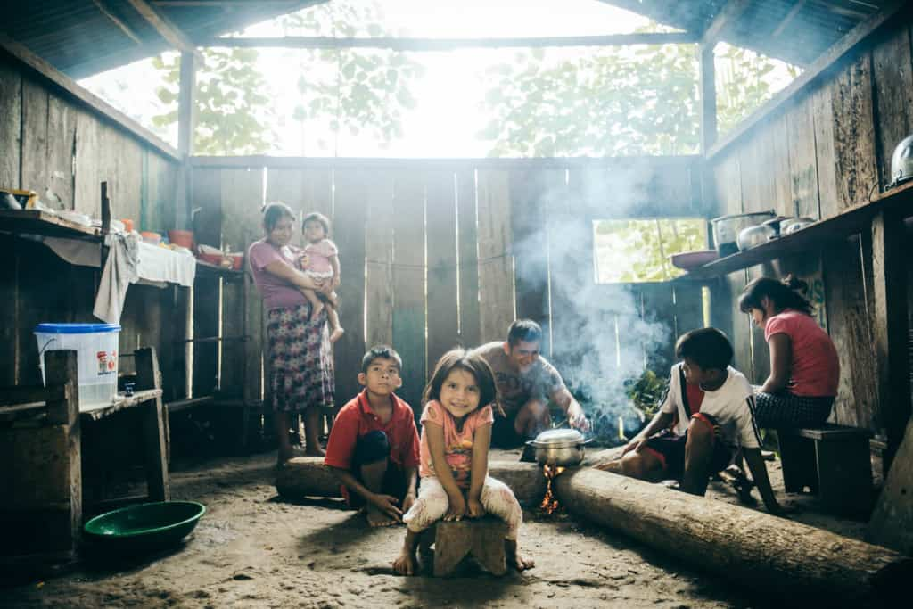 A family of boys, girls, mother holding a baby and father are inside a house with wood plank walls. A man tends to a silver pot cooking over a flame between three logs and a smiling girl in a pink shirt and white pants sits on a stool. Smoke rises from the fire.