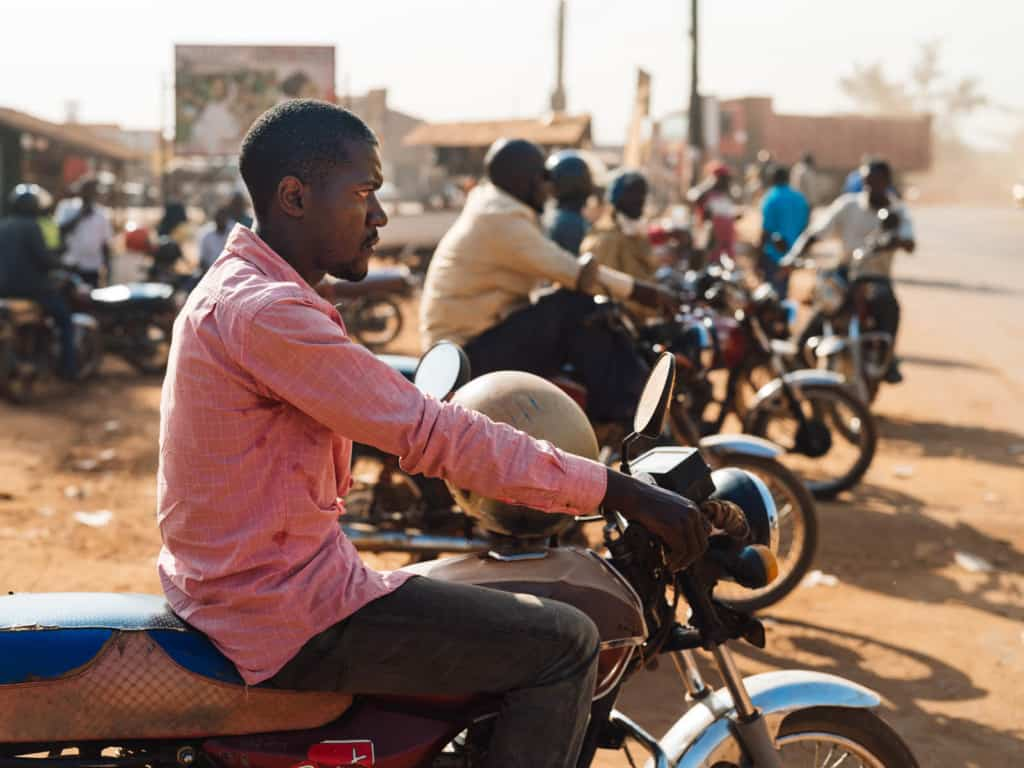 Boda driver (motorcycle taxi) is wearing a pink shirt and sitting on a motorcycle. There are more men on motorcycles in the background. Driving a boda is their primary source of income.