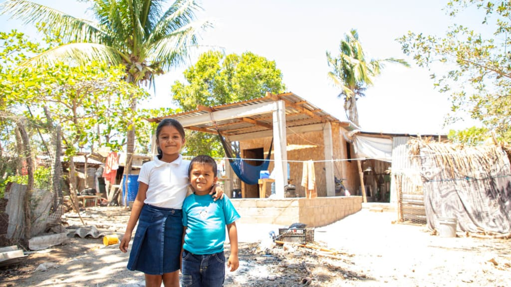 A girl wearing a blue skirt and a white shirt. She has her arm around her brother who is wearing a blue shirt. They are standing outside their new home.
