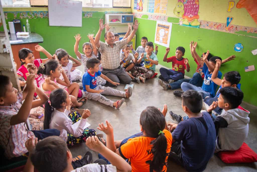 Pastor Agapito is praying with the children in one of the church classrooms. The walls are green with colorful decorations. Pastor Agapito and the children are raising their hands in the air.