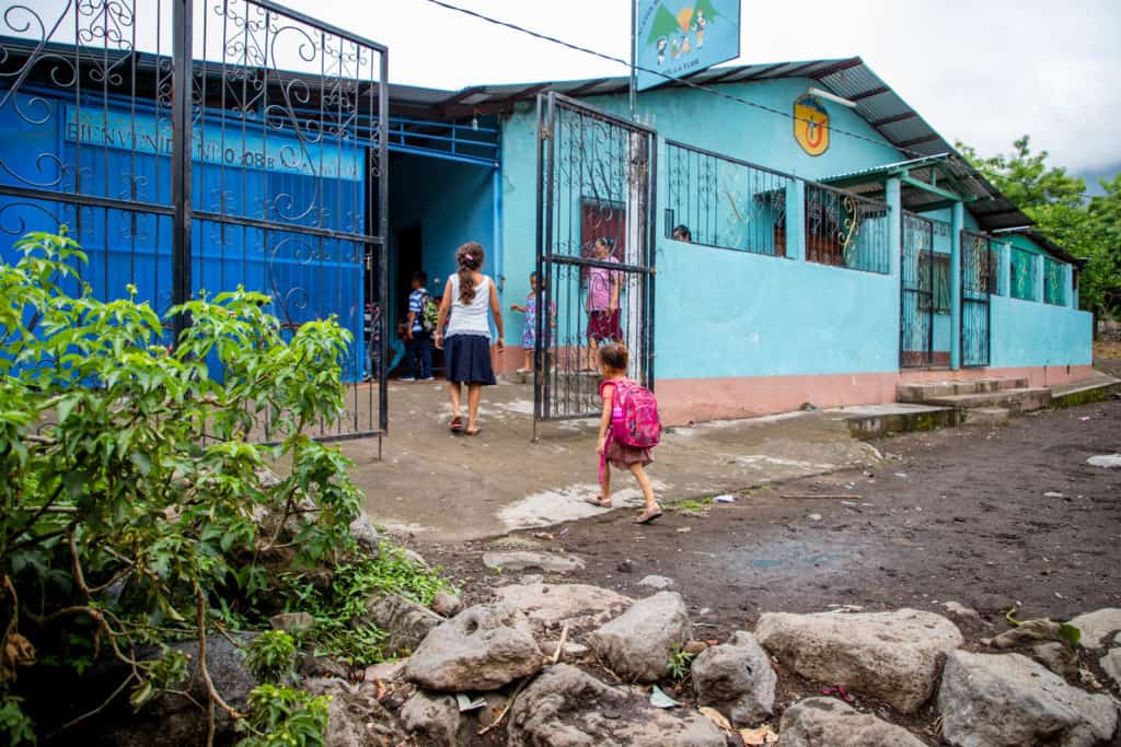 Girl walking into the Compassion project carrying a pink backpack. The building is blue and there is a wrought iron fence surrounding it.