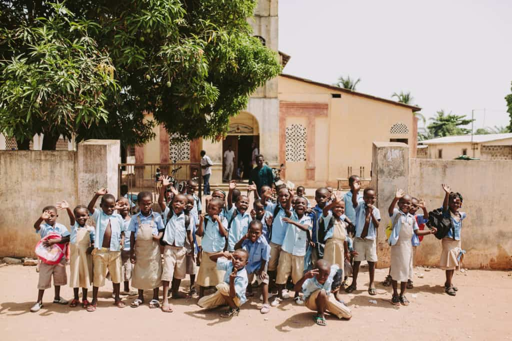 A group of boys and girls children students wearing school center uniform blue shirts and either brown dresses or pants stand together outside waving with arms and hands in the air staring posing all together outside the front of the church center with the building in the background gate and concrete wall.