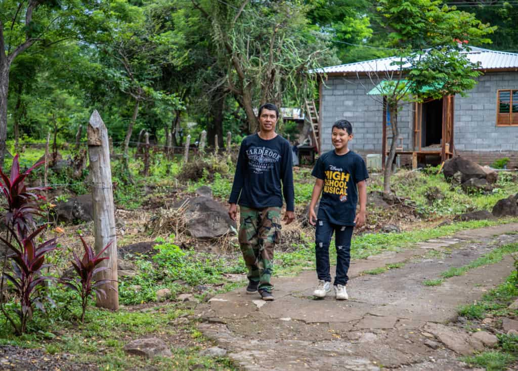 Boy wearing a black shirt, ripped jeans, and white tennis shoes. His father (left) is wearing a black, long sleeved shirt, camo pants and black shoes. They are walking together down a dirt road with their house behind him.