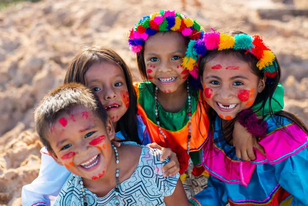 Four children are dressed in colorful outfits and have red paint on their faces. They are standing outside with their arms around each other.