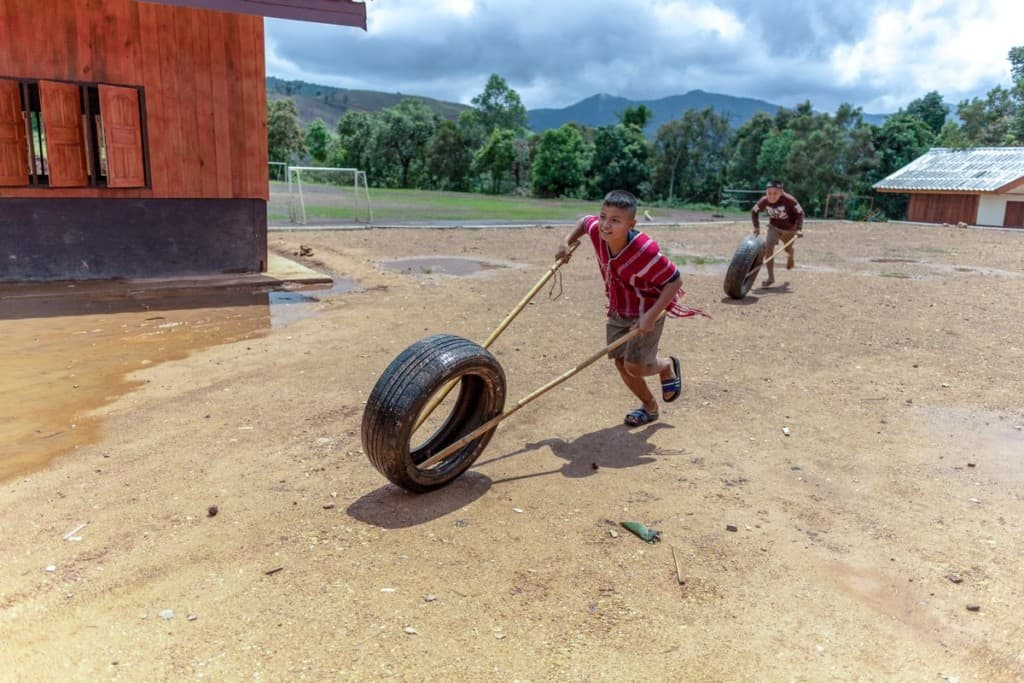 A boy wearing a red and white shirt, shorts and sandals uses bamboo poles to hold up the wheel of a car tire while running outside. Another boy is running after him with his own tire and bamboo poles.