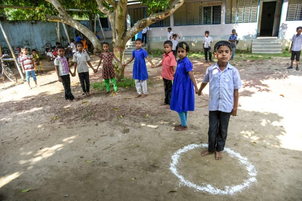 Seven children stand in a line outdoors in Bangladesh. They are holding hands. One boy stands in a circle drawn from white chalk. The children are playing the game golla choot