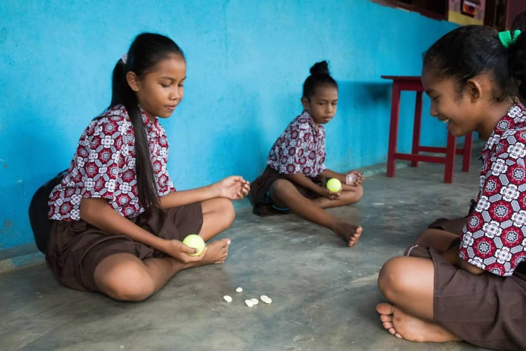 Three girls sit on a clean concrete floor in front of a blue wall. They are playing the game of bola bekel. Two are holding yellow balls in their hands. There are six small seashells on the floor between them.