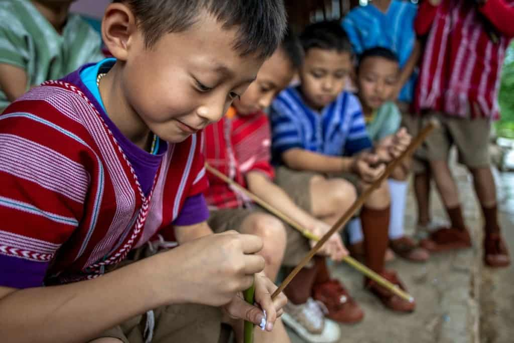 Children in Thailand load their bamboo shoots with wet paper, getting ready to play boe-thor.