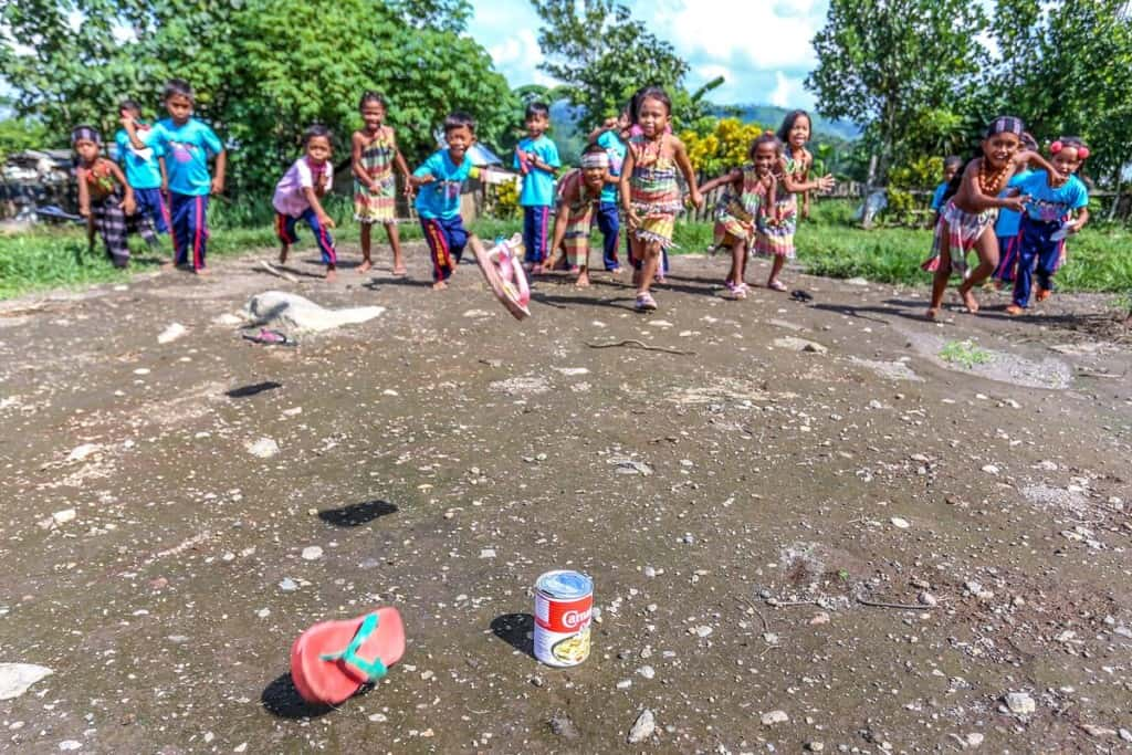 Children in Thailand throw flip-flops at a tin can, playing the game tumbang preso