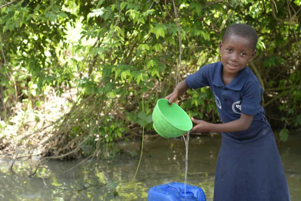 Girl wearing her Compassion uniform, a blue shirt and skirt. She is getting water from a river with a green bowl and is pouring it into a larger blue container.
