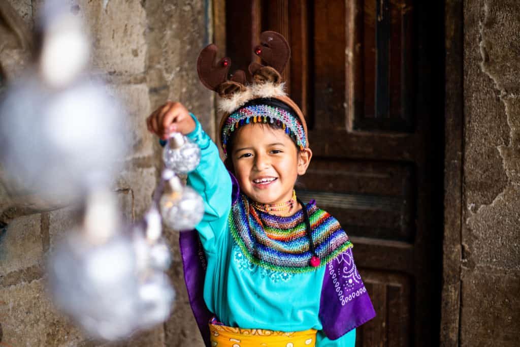Girl at her home holding Christmas ornaments. She is wearing traditional clothes and a reindeer hat.