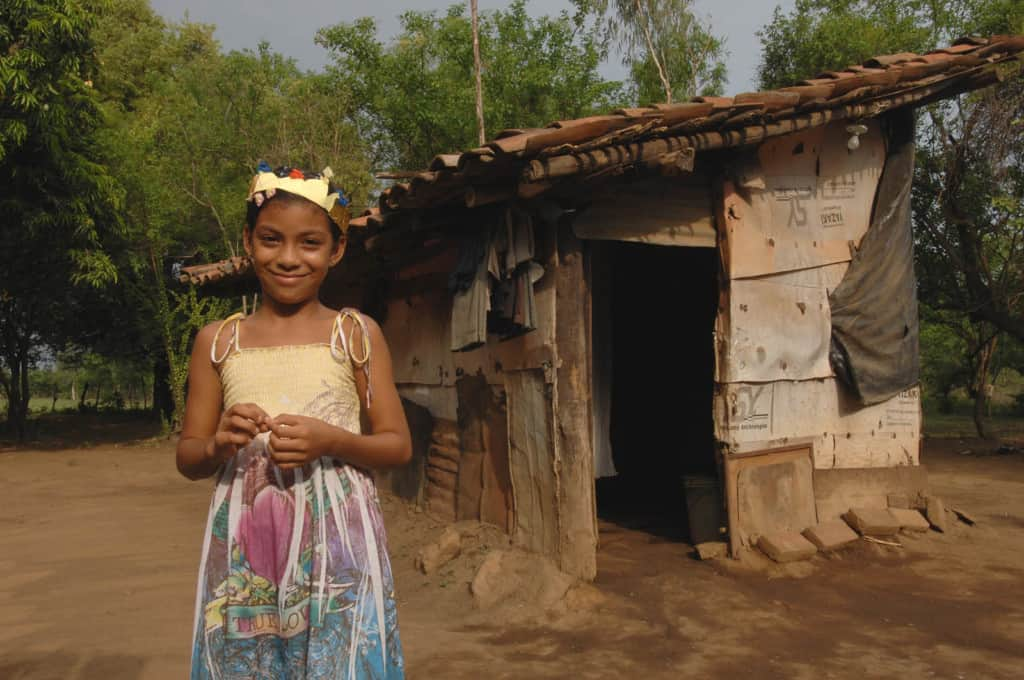 Girl standing in front of home that is constructed with cardboard pieces and black tarp. The roof has tile pieces. She is wearing a sun dress and a gold crown on her head.