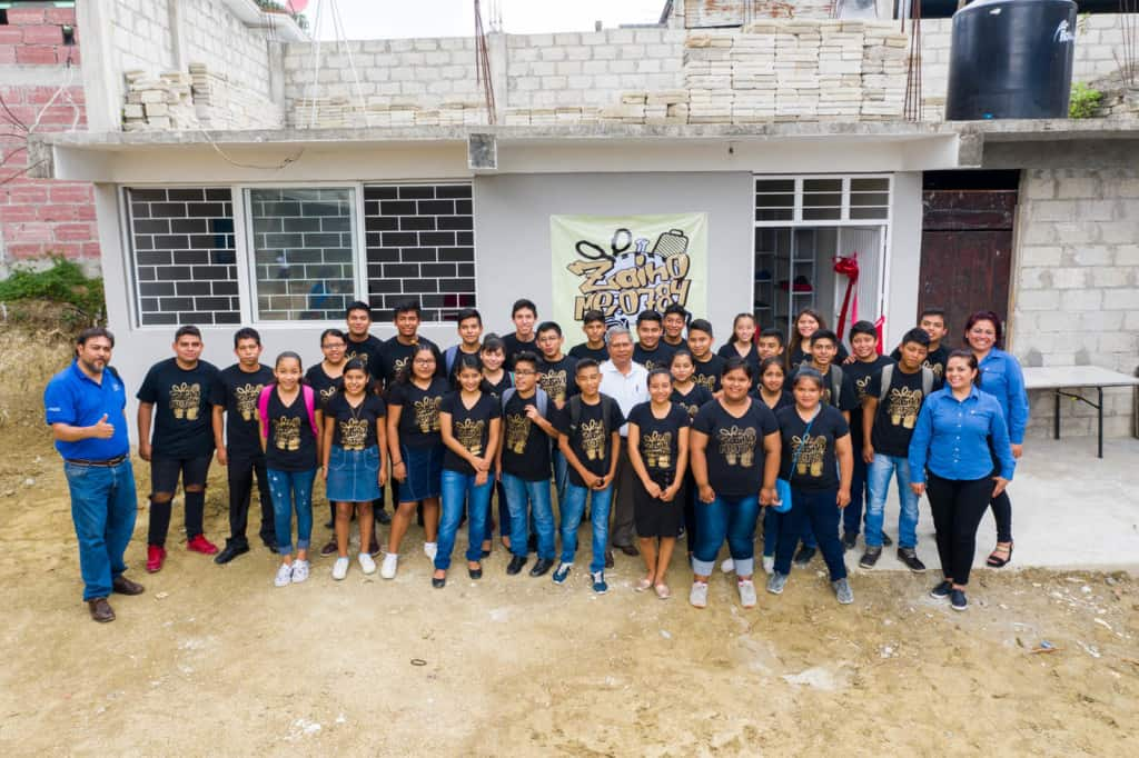 Youths (in black shirts) and tutors (in blue shirts) involved in the backpack production project are standing in front of the new center that was built for this project. The building is white.