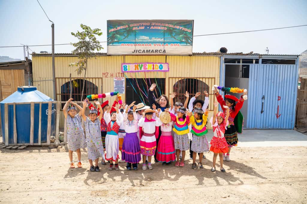 Compassion Peru's national director posing with children in front a church. The children are smiling and waving while wearing brightly colored clothing.