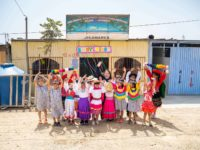 Compassion Peru's national director posting with children in front a church. The children are smiling and waving while wearing brightly colored clothing.