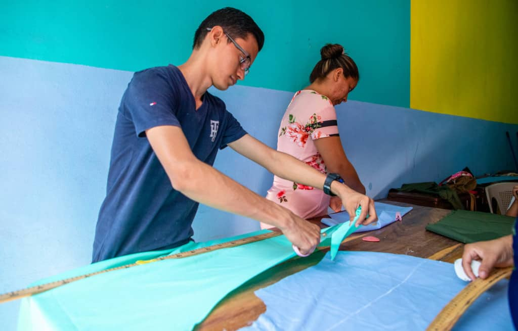 Victor, in a blue shirt, is standing at a work table cutting a piece of green fabric.