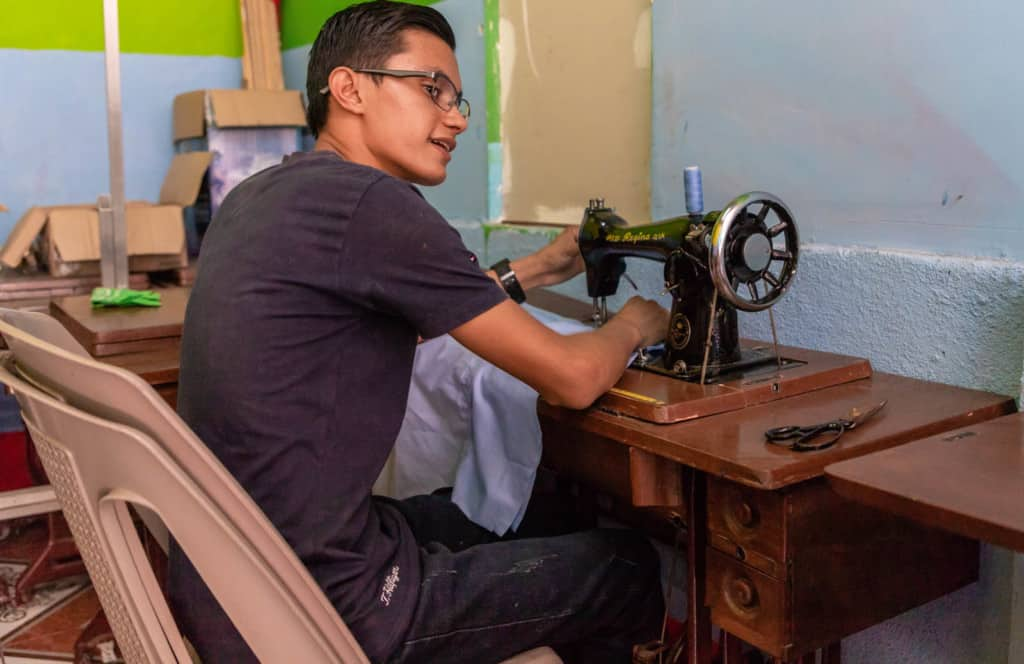 Victor, in a black shirt and jeans, is sitting at a sewing machine table in the classroom used for the sewing workshop. The walls are green and blue.