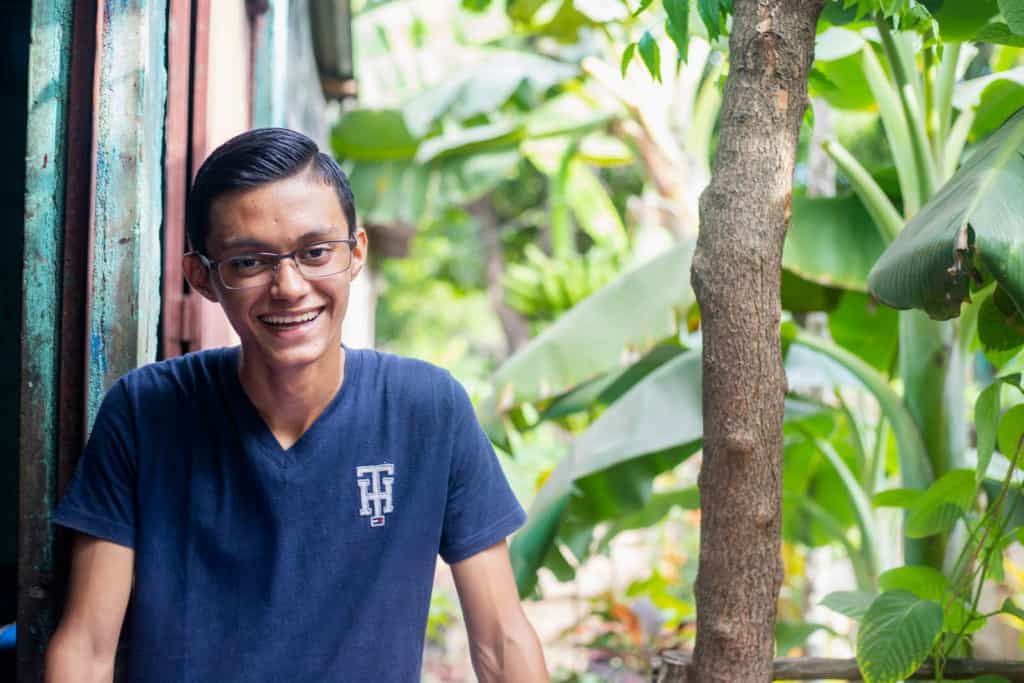 Victor, in a blue shirt, is smiling and standing outside his home. There are tropical trees next to him.