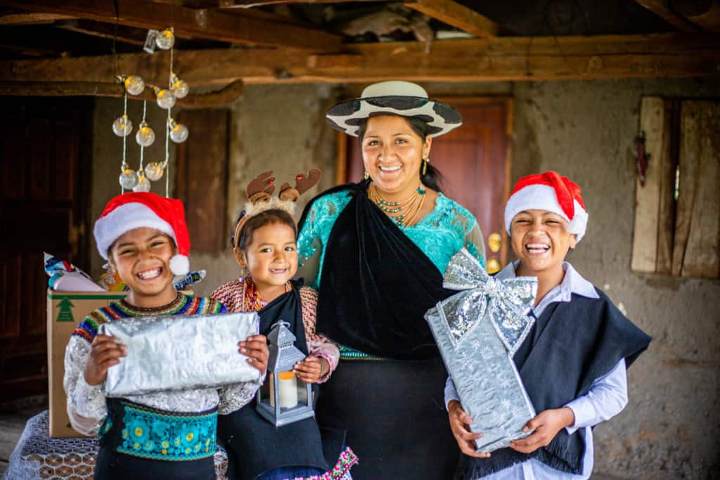 Joselin, Mayte, Jenny (mother), and Javier are inside their home. Two of the children are holding Christmas gifts and they are wearing Christmas hats.