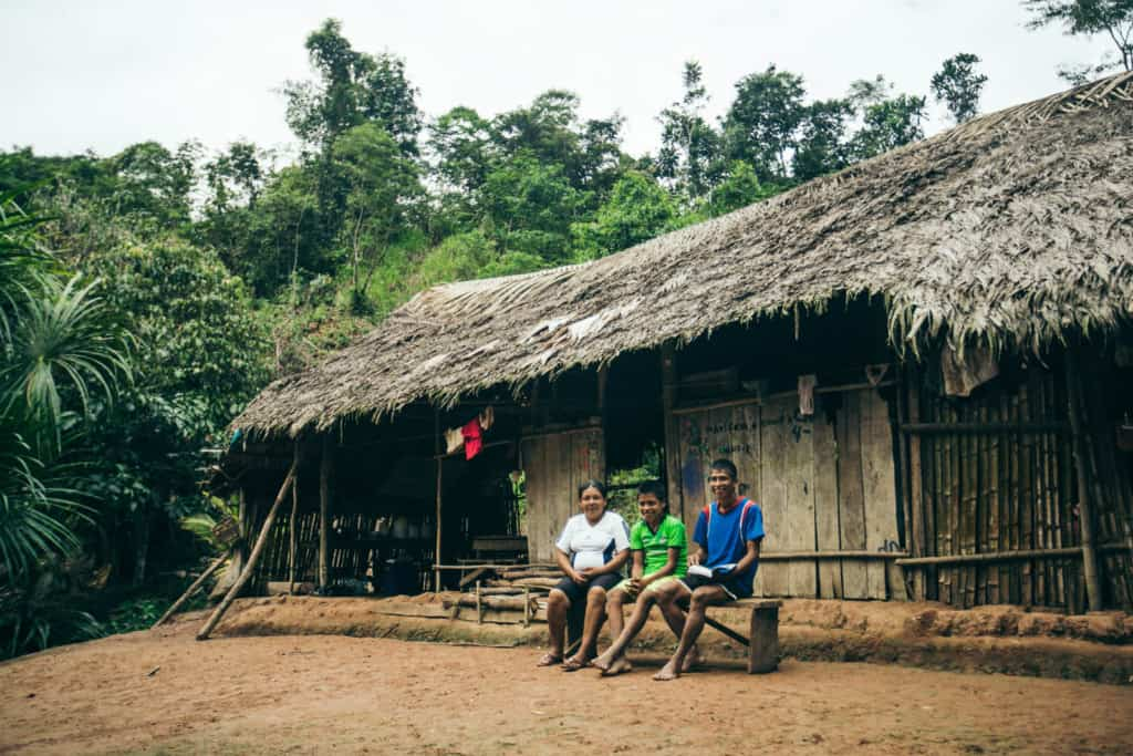 A mother, father and son sit outside in front of a wood home on a bench. They wear white, green and blue shirts. The house has a thatched roof and there are trees in the background.
